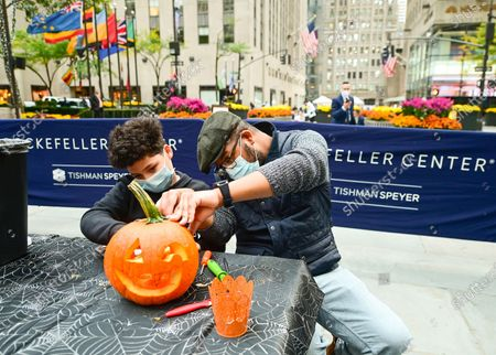 In preparation for Halloween, Sharif Butler and his nephew Chace, 11, carve pumpkins at Rockefeller Center on . People working at Rockefeller Center took a break to learn how to properly carve pumpkins from Maniac Pumpkin Carvers, artists from Brooklyn. The pumpkin carving class was part of Tishman Speyer's ZO. amenities program for all those who work in its buildings