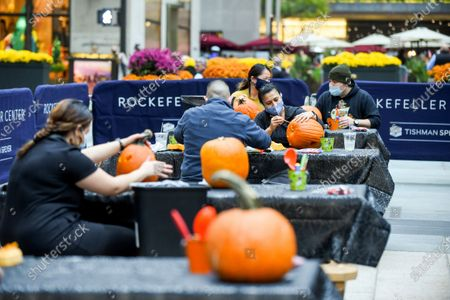 In preparation for Halloween, New Yorkers carve pumpkins at Rockefeller Center on . People working at Rockefeller Center took a break to learn how to properly carve pumpkins from Maniac Pumpkin Carvers, artists from Brooklyn. The pumpkin carving class was part of Tishman Speyer's ZO. amenities program for all those who work in its buildings