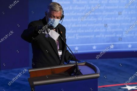 A technician cleans the microphone on US President Donald Trump's podium before the final presidential debate at Belmont University in Nashville, Tennessee, USA, 22 October 2020. This is the last debate between the US President Donald Trump and Democratic presidential nominee Joe Biden before the upcoming presidential election on 03 November.
