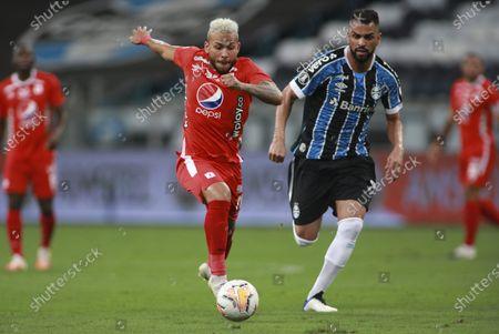 Duvan Vergara of Colombia's America, left, goes with the ball past Maicon of Brazil's Gremio during a Copa Libertadores soccer match at the Gremio Arena in Porto Alegre, Brazil
