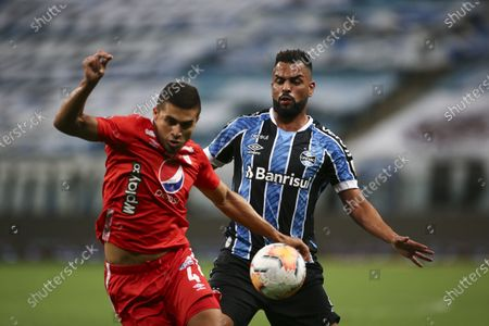 Carlos Sierra of Colombia's America, left, fights for the ball with Maicon of Brazil's Gremio during a Copa Libertadores soccer match at the Gremio Arena in Porto Alegre, Brazil