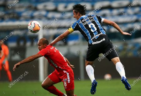 Juan Perez of Colombia's America, left, fights for the ball with Pedro Geromel of Brazil's Gremio during a Copa Libertadores soccer match at the Gremio Arena in Porto Alegre, Brazil