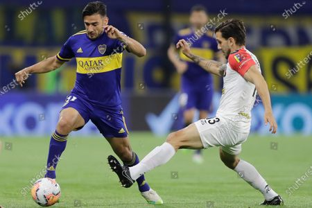 Eduardo Salvio of Argentina's Boca Juniors, left, and Carlos Rivero of Venezuela's Caracas FC battle for the ball during a Copa Libertadores Group H soccer match at the Bombonera stadium in Buenos Aires, Argentina