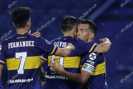 Teammates congratulate Carlos Tevez of Argentina's Boca Juniors, right, after he scored his side's second goal against Venezuela's Caracas FC during a Copa Libertadores Group H soccer match at the Bombonera stadium in Buenos Aires, Argentina