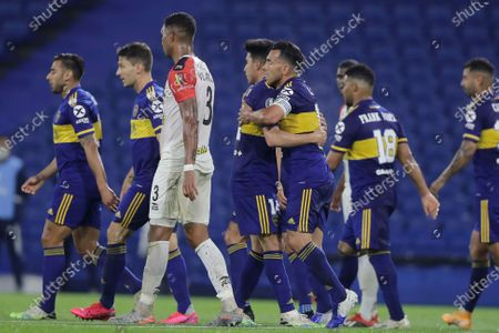 Carlos Tevez of Argentina's Boca Juniors is greeted by teammates after scoring his side's second goal against Venezuela's Caracas FC during a Copa Libertadores Group H soccer match at the Bombonera stadium in Buenos Aires, Argentina