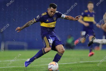 Carlos Tevez of Argentina's Boca Juniors scores his side's third goal during a Copa Libertadores Group H against Venezuela's Caracas FC soccer match at the Bombonera stadium in Buenos Aires, Argentina