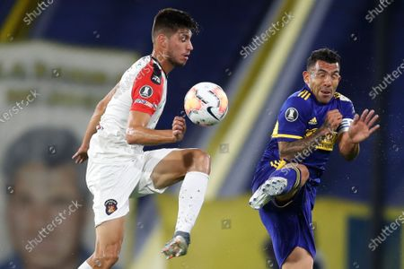 Diego Osio of Venezuela's Caracas FC, left, and Carlos Tevez of Argentina's Boca Juniors battle for the ball during a Copa Libertadores Group H soccer match at the Bombonera stadium in Buenos Aires, Argentina