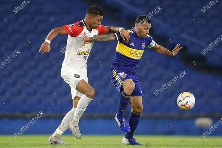 Rosmel Villanueva of Venezuela's Caracas FC grabs Carlos Tevez of Argentina's Boca Juniors during a Copa Libertadores Group H soccer match at the Bombonera stadium in Buenos Aires, Argentina