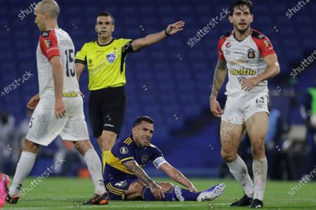 Referee Christian Ferreyra, of Uruguay, rules a fouls against Carlos Tevez of Argentina's Boca Juniors during a Copa Libertadores Group H soccer match against Venezuela's Caracas FC at the Bombonera stadium in Buenos Aires, Argentina