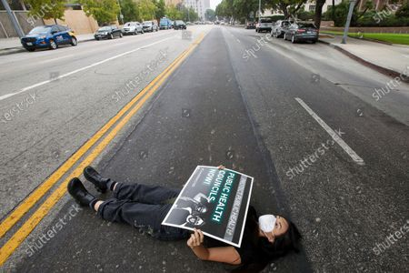 Stock Image of Natasha Wong lies on Temple Avenue during a die-in rally by essential workers, clergy members, parents and other community members and a memorial service to honor the thousands of people who have died because of COVID-19. The demonstrators call on the Los Angeles County Board of Supervisors to establish public health councils to prevent further deaths. Rally took place in front of Kenneth Hahn Hall of Administration on Wednesday, Oct. 21, 2020 in Los Angeles, CA. (Irfan Khan / Los Angeles Times)