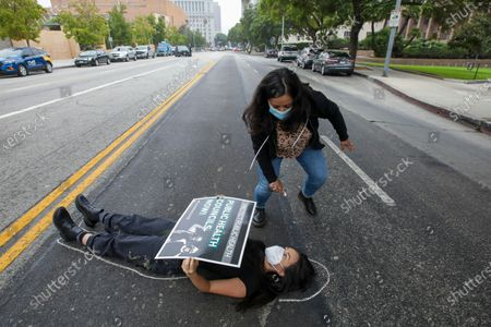 Andrea Gonzalez draws a body line as a protestor Natasha Wong lies on Temple Avenue during a die-in rally by essential workers, clergy members, parents and other community members and a memorial service to honor the thousands of people who have died because of COVID-19. The demonstrators call on the Los Angeles County Board of Supervisors to establish public health councils to prevent further deaths. Rally took place in front of Kenneth Hahn Hall of Administration on Wednesday, Oct. 21, 2020 in Los Angeles, CA. (Irfan Khan / Los Angeles Times)