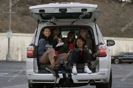 Stephanie Liu, from left, Christina Huang, Jessica Nyquist, Hanseul Nam and Laura Halsey watch from their vehicle as President Donald Trump and Democratic presidential candidate former Vice President Joe Biden speak during a Presidential Debate Watch Party at Fort Mason Center in San Francisco, . The debate party was organized by Manny's, a San Francisco community meeting and learning place