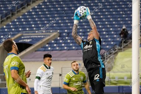 Portland Timbers goalie Steve Clark leaps to snag the ball against the Seattle Sounders in the first half of an MLS soccer match, in Seattle