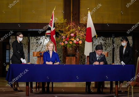 British Secretary of State for International Trade Elizabeth Truss (2-L) signs a document with Japanese Foreign Minister Toshimitsu Motegi (2-R) for economic partnership between Japan and Britain at Iikura Annex of the Foreign Ministry in Tokyo, Japan, 23 October 2020.