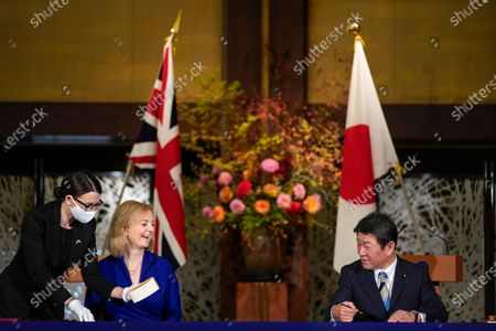 British Secretary of State for International Trade Elizabeth Truss (2-L) signs a document with Japanese Foreign Minister Toshimitsu Motegi (R) for economic partnership between Japan and Britain at Iikura Annex of the Foreign Ministry in Tokyo, Japan, 23 October 2020.
