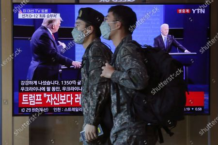 "South Korean army soldiers pass by a TV screen showing a live broadcast of U.S. President Donald Trump, left, and Democratic presidential candidate former Vice President Joe Biden during the final presidential debate, at the Seoul Railway Station in Seoul, South Korea, . The Korean letters read ""U.S. presidential election TV debate"