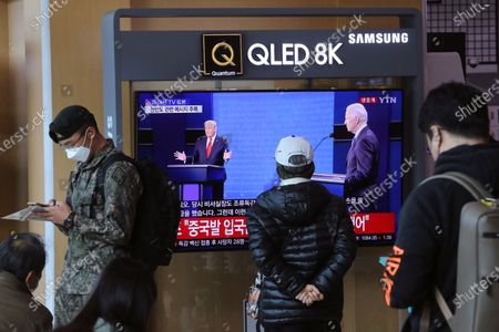 "Screen shows a live broadcast of U.S. President Donald Trump, left, and Democratic presidential candidate former Vice President Joe Biden during the final presidential debate, at the Seoul Railway Station in Seoul, South Korea, . The Korean letters read ""U.S. presidential election TV debate"