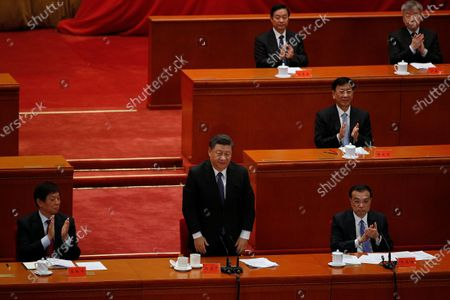 Party officials applaud as Chinese President Xi Jinping, standing, delivers his speech at the commemorating conference on the 70th anniversary of the Chinese army entering North Korea to resist the U.S. army, at the Great Hall fo the People in Beijing