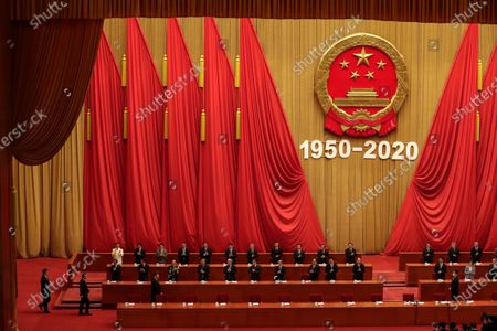 Party officials applaud as Chinese President Xi Jinping, third from left in front row, followed by Premier Li Keqiang, arrives for the commemorating conference on the 70th anniversary of the Chinese army entering North Korea to resist the US army, at the Great Hall fo the People in Beijing