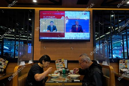 Screen broadcasts Chinese President Xi Jinping during a rally in Beijing, left, and U.S. President Donald Trump speaking at the presidential debate, right, at a restaurant in Hong Kong