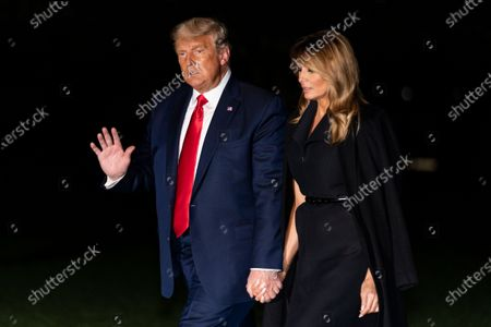 President Donald Trump, accompanied by first lady Melania Trump, waves as he walks from Marine One on the South Lawn of the White House, early, in Washington. Trump is returning from a debate in Nashville, Tenn