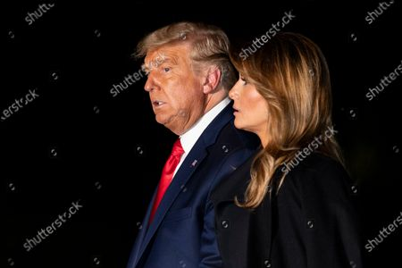 President Donald Trump, accompanied by first lady Melania Trump, walks from Marine One on the South Lawn of the White House, early, in Washington. Trump is returning from a debate in Nashville, Tenn