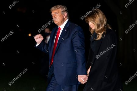 President Donald Trump, accompanied by first lady Melania Trump, pumps his fist as he walks from Marine One on the South Lawn of the White House, early, in Washington. Trump is returning from a debate in Nashville, Tenn