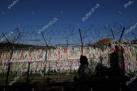 Woman wearing a face mask as a precaution against the coronavirus, walks near the wire fences decorated with ribbons written with messages wishing for the reunification of the two Koreas at the Imjingak Pavilion in Paju, South Korea, . The second U.S. presidential debate between President Donald Trump and Democratic presidential candidate, former Vice President Joe Biden, was held on Thursday