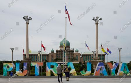 Women take pictures in front of the prime minister's office building in Putrajaya, Malaysia, . Malaysian opposition leader Anwar Ibrahim said Friday he was concerned about reports that Prime Minister Muhyiddin Yassi may invoke emergency laws to suspend Parliament and stymie bids to oust his government