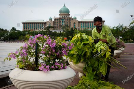 Worker cleans in front of the prime minister's office building in Putrajaya, Malaysia, . Malaysian opposition leader Anwar Ibrahim said Friday he was concerned about reports that Prime Minister Muhyiddin Yassi may invoke emergency laws to suspend Parliament and stymie bids to oust his government
