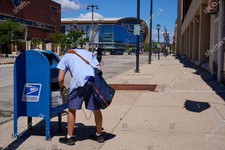 A postal worker empties a box near the Fiserv Forum in Milwaukee. U.S. Postal Service records show delivery delays have persisted across the country as millions of Americans began voting by mail, raising the possibility of ballots being rejected because they arrive too late. Parts of the politically coveted battleground states of Wisconsin, Michigan, Pennsylvania and Ohio fell short of delivery goals by wide margins as the agency struggles to regain its footing after a tumultuous summer