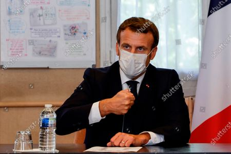 """French President Emmanuel Macron chairs a meeting with the medical staff of the Rene Dubos hospital center, in Pontoise, outside Paris, . French Prime Minister Jean Castex said Thursday a vast extension of the nightly curfew that is intended to curb the spiraling spread of the coronavirus, saying """"the second wave is here."""" The curfew imposed in eight regions of France last week, including Paris and its suburbs, is being extended to 38 more regions and Polynesia"""