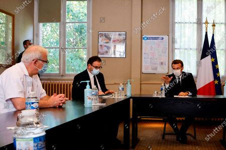"""French President Emmanuel Macron, right, chairs a meeting with the medical staff of the Rene Dubos hospital center, in Pontoise, outside Paris, . French Prime Minister Jean Castex said Thursday a vast extension of the nightly curfew that is intended to curb the spiraling spread of the coronavirus, saying """"the second wave is here."""" The curfew imposed in eight regions of France last week, including Paris and its suburbs, is being extended to 38 more regions and Polynesia"""