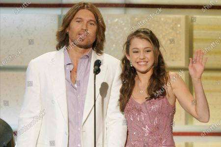"""Billy Ray Cyrus and his daughter, actress Miley Cyrus, present an award during the 41st Academy of Country Music Awards in Las Vegas. On Friday, Oct. 23, 2020, The Associated Press reported on stories circulating online incorrectly asserting at a Miley Cyrus concert in 1993, the pop singer told a 9-year-old girl that anything was possible as long as you believed in God. The little girl said she believed in God and was going to become famous one day by stopping Obamacare and making it illegal to kill babies. That little girl grew up to be Judge Amy Coney Barrett, who has been nominated to a Supreme Court seat. Cyrus was born in 1992 and was only 1 year old in 1993. Barrett, a 48-year-old judge, began her legal career in the late 1990s, when Cyrus was still a child. The Affordable Care Act, also known as """"Obamacare,"""" was not enacted until 2010"""