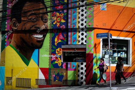 Stock Photo of People walk by a mural depicting Pele, by the Brazilian artist Aleksandro Reis, in Sao Paulo, Brazil, 23 October 2020. Legendary Brazilian soccer player Edson Arantes do Nascimento, known as Pele, turned 80 on 23 October.