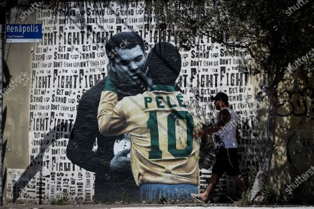 A man walks by a mural depicting Pele embracing Muhammad Ali, by the Brazilian street artist Luis Bueno, in Sao Paulo, Brazil, 23 October 2020. Legendary Brazilian soccer player Edson Arantes do Nascimento, known as Pele, turned 80 on 23 October.
