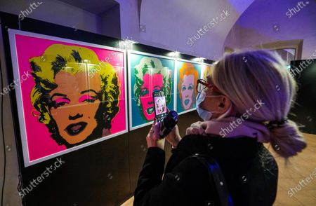Stock Picture of A visitor takes pictures of portraits of US actress Marilyn Monroe by US artist Andy Warhol are on display in the Andy Warhol exhibition, entitled 'Super Pop,' in Nichelino, near Turin, Italy, 23 October 2020. The exhibit runs at the Palazzina di caccia of Stupinigi from 24 October 2020 to 31 January 2021.