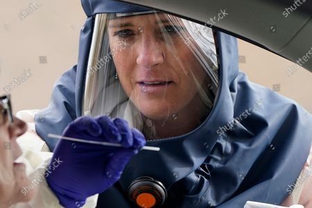 """Salt Lake County Health Department public health nurse Lee Cherie Booth performs a coronavirus test outside the Salt Lake County Health Department, in Salt Lake City. Utah hit another ominous record by tallying the highest number of confirmed coronavirus cases in a single day as the state struggles to slow a monthlong surge of COVID-19 that is filling intensive care beds at hospitals. Gov. Gary Herbert warned in a statement that the state is """"on the brink,"""" and once again pleaded with people to adhere to mask mandates in place in most counties in the state"""