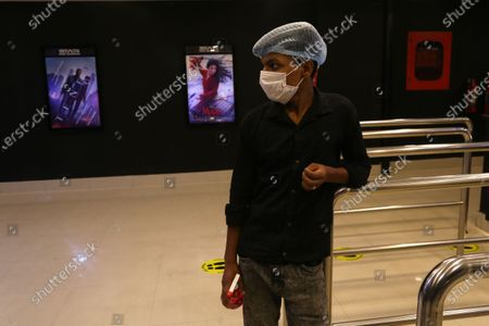 A staff wearing personal protective equipment stand guard at entrance of ticket counter to disinfect the audience hand