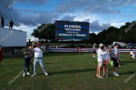 Supporters of President Donald Trump take photos as he speaks during a campaign rally at The Villages Polo Club, in The Villages, Fla