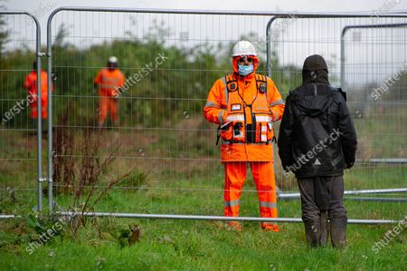 A protester tries to talk to an HS2 security guard. HS2 were tree felling in Grim's Ditch today near to Jones Hill Wood. Anti HS2 environmental campaigners allege that HS2 do not have the correct licence for felling at Grim's Ditch and so were possibly committing a wildlife crime. Previous archaeological investigations into Grim's Ditch, a haven for wildlife, date it back as far as the Iron Age. The hugely controversial HS2 High Speed Rail from London to Birmingham link puts 108 ancient woodlands, 33 SSSIs and 693 wildlife areas at risk