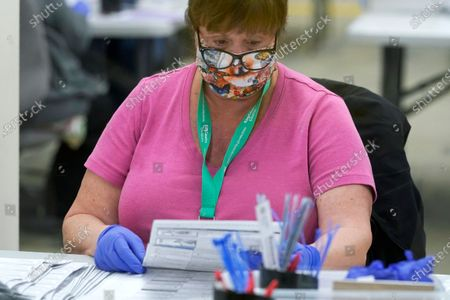 Worker at the King County election headquarters in Renton, Wash., wears a mask as she processes ballots at an opening station, . Washington is a vote by mail state, and thousands of ballots have already been mailed back, dropped off in boxes, or cast in person. Although counting has begun, no results will be known to workers or released until the night of election day