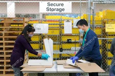 """Workers at the King County election headquarters in Renton, Wash., assemble boxes in front of a chain-link """"cage"""" where ballots and and other materials are securely stored, . Washington is a vote by mail state, and thousands of ballots have already been mailed back, dropped off in boxes, or cast in person. Although counting has begun, no results will be known to workers or released until the night of election day"""