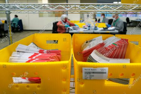 Boxes of vote-by-mail ballot envelopes are shown at the King County election headquarters in Renton, Wash., . Washington is a vote by mail state, and thousands of ballots have already been mailed back, dropped off in boxes, or cast in person. Although counting has begun, no results will be known to workers or released until the night of election day