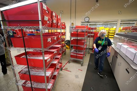 Worker at the King County election headquarters in Renton, Wash., walks near trays of ballots being loaded into a sorting machine, . Washington is a vote by mail state, and thousands of ballots have already been mailed back, dropped off in boxes, or cast in person. Although counting has begun, no results will be known to workers or released until the night of election day