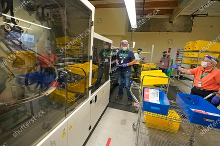 Workers at the King County election headquarters in Renton, Wash., handle trays of ballots near a sorting machine, . Washington is a vote by mail state, and thousands of ballots have already been mailed back, dropped off in boxes, or cast in person. Although counting has begun, no results will be known to workers or released until the night of election day