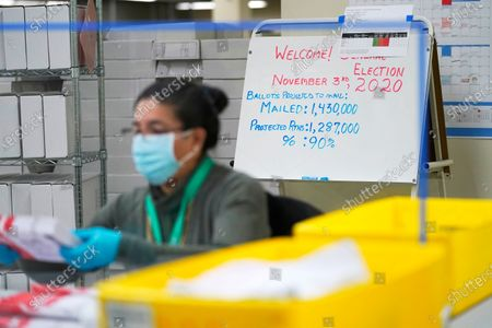 Worker at the King County election headquarters in Renton, Wash., processes ballots near a poster that predicts a 90% voter turnout in the upcoming election, . Washington is a vote by mail state, and thousands of ballots have already been mailed back, dropped off in boxes, or cast in person. Although counting has begun, no results will be known to workers or released until the night of election day