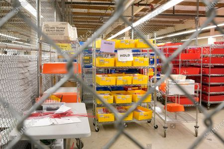 Boxes of ballots and envelopes are shown in a secure storage area at the King County election headquarters in Renton, Wash., . Washington is a vote by mail state, and thousands of ballots have already been mailed back, dropped off in boxes, or cast in person. Although counting has begun, no results will be known to workers or released until the night of election day
