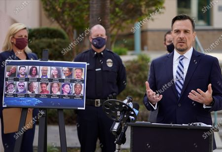 Assistant U.S. Attorney Christopher Grigg, chief of the Central California District's national security division, at the podium, talks to reporters next to portraits of the 14 victims in a 2015 terror attack in San Bernardino, California, outside federal court in Riverside, Calif., . Enrique Marquez Jr. was sentenced to 20 years in prison Friday for supplying the rifles used by his friend Syed Rizwan Farook and Farook's wife to open fire on a gathering of Farook's co-workers from San Bernardino County nearly five years ago. After killing 14 people and wounding 22, Farook and his wife were killed in a gun battle with authorities