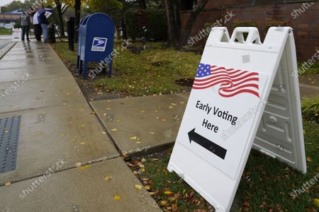 An information sign shows outside the Elk Grove Village Hall as voters wait in line during early voting at Elk Grove Village, Ill., . The US early voting total in 2020 has already exceeded the number of early votes cast in 2016 and there are still 11 more days to go until Election Day